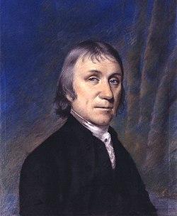 Kvaron-longa portreto de viro en nigra mantelo kontraŭ purpura kaj blua kurtenfono.
