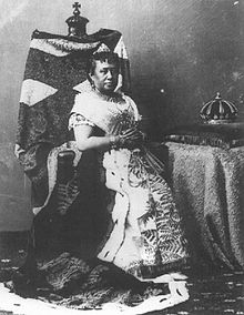Photograph of Queen Kapiʻolani seated on a chair with her crown on a table to the right