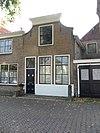 Huis met ingezwenkte lijstgevel met stoep en stoeppaal
