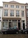 foto van Huis met geelgeverfde lijstgevel, hoog opgetrokken voor lager pand