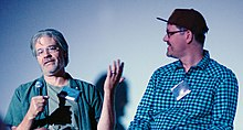 Two men with glasses seated on a stage, with microphones. One is talking and gesturing, and the other is looking at him.