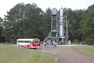 U.S. Space & Rocket Center - A tour bus waits as tourists inspect the Redstone Test Stand on a 2012 tour of Marshall Space Flight Center.