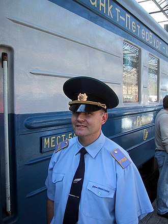 "Conductor (rail) - A Russian train conductor in front of the express train ""Repin"""