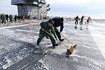 Sailors scrub aqueous film forming foam off of the flight deck of PCU Gerald R. Ford (CVN 78). (33648165750).jpg
