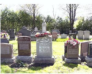 Cemetery headstone among others, with flowers