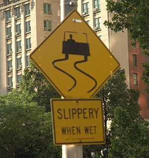 Sliding (motion) - Slippery when wet signs alert drivers that they need to slow down because the kinetic friction between the tires and a wet surface is much less than that of a dry surface.