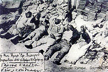 Photograph of corpses lined up on the street. Some are visibly burned.