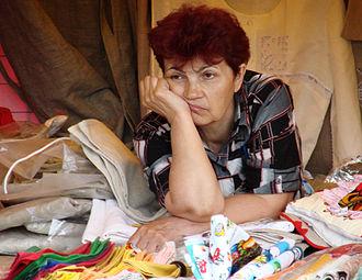 Boredom - A souvenir seller appears bored as she waits for customers.