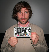 "A man in a pink dress shirt and tan jacket holding up a producer credit for ""The 1 Second Film"" (as indicated by the text)."