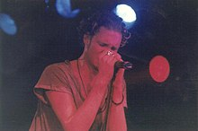 A male singer, Layne Staley, singing into a microphone at a concert. His eyes are closed as he sings. He is wearing rings on his left hand.