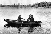 Foto av en liten kano på en innsjø med tre personer i.  Khrusjtsjov roer.