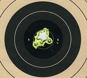 "Shooting sports - A round shooting target with several hits in the center, which is called ""bullseye""."