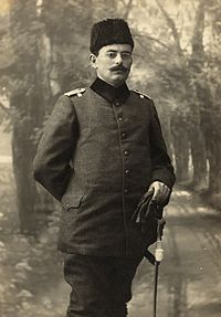 A man in an Ottoman army uniform, sporting a full moustache, and wearing a wool hat and round spectacles. He carries what appear to be gloves in his left hand. His right arm is bent and his right hand rests on the small of his back.
