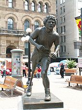 Statue of a runner with an artificial leg partially hunched forward.
