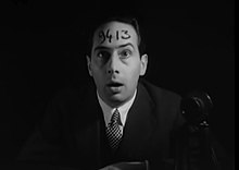 "A man wearing a suit jacket and tie stares forward with a shocked and confused facial expression, with the numbers ""9413"" written across his forehead."