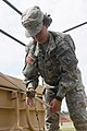 U.S. Army Pfc. Dawnn Weston, a chemical operations specialist with the 108th Chemical Company, South Carolina Army National Guard, connects two pipes together as part of a decontamination center during Ardent 130518-Z-WS267-001.jpg