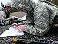 U.S. Army soldiers plot eight-digit grid coordinates on a map before participating in a daytime land navigation course while competing for the Expert Field Medical Badge at Joint Base Lewis-McChord, Wash 130410-A-FS521-227.jpg