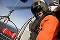 U.S. Coast Guard Petty Officer 2nd Class Miguel Arellano, an aviation maintenance technician, operates the hoist on an MH-65C Dolphin helicopter during training operations off the coast of Venice, Calif., Jan 120124-G-MR731-006.jpg