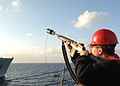 U.S. Navy Gunner's mate 1st Class Zack Maciejewski prepares to fire a shot line from the guided missile destroyer USS Mitscher (DDG 57) to the fleet replenishment oiler USNS Leroy Grumman (T-AO-195) during an 110120-N-XQ375-017.jpg