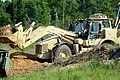 U.S. Soldiers assigned to the 1782nd Engineer Company, South Carolina Army National Guard, use a high mobility engineer excavator front loader to clear a road blocked by downed trees and crushed vehicles during 130518-Z-WT236-004.jpg