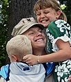 US Navy 020703-N-5576W-001 Utilitiesman 1st Class Daniel Heathfield gets a big hug from his children at the main gate to Naval Station, Great Lakes.jpg