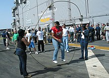 Picture of US service personnel jumping double Dutch on the deck of an aircraft carrier