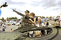 US Navy 040803-N-6477M-125 Master At Arms 2nd Class Michael Hinton, assigned to Naval Station Everett, helps local children enjoy their topside view of a Highly Mobile Multipurpose Wheeled Vehicle (HMMWV).jpg