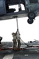 US Navy 050104-M-5578G-042 Gunnery Sgt. Flan Harrell, left, and Lance Cpl. James E. Miller, attach a cargo pennant to a MH-60S Knighthawk helicopter.jpg