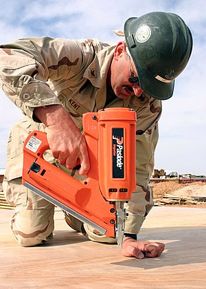 Nail gun - Image: US Navy 050425 N 8102P 003 Utilitesman 2nd Class John Kent, assigned to Naval Mobile Construction Battalion Two Four (NMCB 24), uses a nail gun as he helps to in build Southwest Asia huts at Camp Korean Village, in western Iraq
