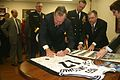 US Navy 060114-N-0191T-038 The 41st President of the United States, the Honorable George H.W. Bush autographs a basketball jersey for the crew of USS San Antonio (LPD 17).jpg