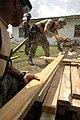 US Navy 070624-N-6278K-006 Steelworker 3rd Class Joel Washington, left, and Builder 2nd Class William Lathan, Construction Battalion Maintenance Unit (CBMU) 202, saw a board for a sidewalk at Belize Rural High School.jpg