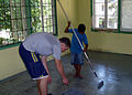 US Navy 070910-N-7111B-003 Seaman Harley Nelson, stationed aboard the guide-missile frigate USS Halyburton (FFG 40), receives some assistance while painting a floor during a community relations project at Provida Home.jpg