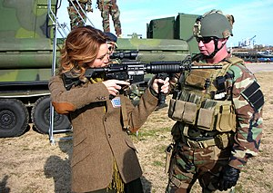 Hilarie Burton - Burton holding an M4 carbine during a USO visit.