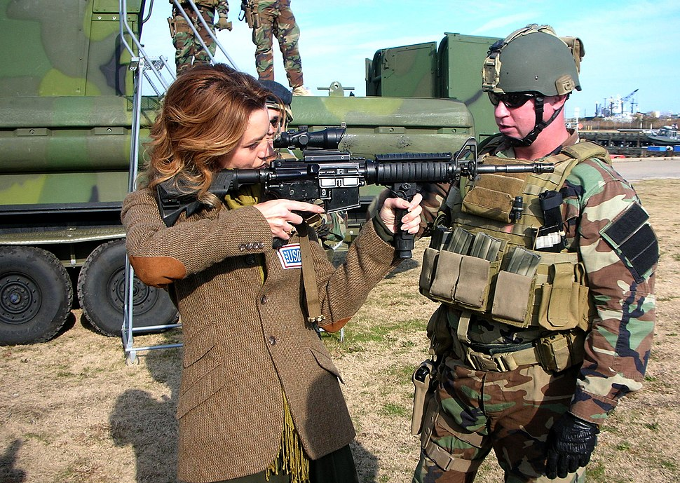 US Navy 081206-N-3346C-012 Chief Master-at-Arms Michael Minotto explains the functions of the M4 Battle Rifle to actress Hilarie Burton