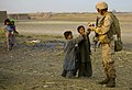 US Navy 091029-M-2581P-478 Hospital Corpsman 3rd Class Eric Nobriga, assigned to Combined Anti-Armor Team 2 (CAAT 2), hands candy to Afghan children during a patrol in Nawa District.jpg