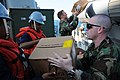 US Navy 100118-N-7923C-004 Hospital Corpsman 1st Class Robert Lemon, assigned to Maritime Civil Affairs Team (MCAT) 203, helps load food and medical supplies aboard a rigid hull inflatable boat.jpg