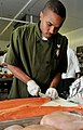 US Navy 100428-N-5812W-003 Culinary Specialist 3rd Class Corey Hartfield prepares a filet of farm-raised pacific steelhead salmon.jpg