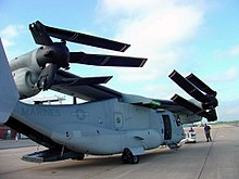 A V-22 with its wing rotated 90 degrees so it runs the length of the fuselage.