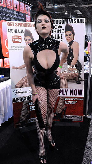 "Dominatrix - A dominatrix wearing typical rubber latex dress, fishnet stockings and stiletto heels. She is holding a spanking paddle. Behind her is a board on top of which is written ""Get Spanked Here"". Photo from AVN Adult Entertainment Expo, 2011"