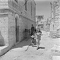 Vrouw met een kind aan de hand na een bezoek aan de bakker die zijn brood op str, Bestanddeelnr 255-1194.jpg