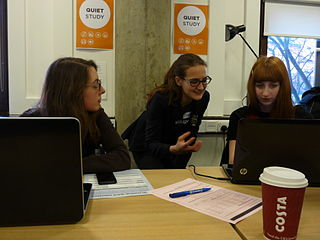 The photograph shows three women at a computer screen, having a conversation