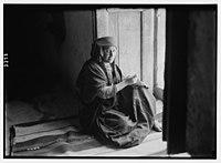 Wady Shaib Es-Salt, Amman, etc. Christian Bedouin girl of Es-Salt, sitting in doorway, sewing. LOC matpc.02737.jpg