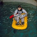 Wally Schirra floats on a one-man life raft during water egress training.jpg