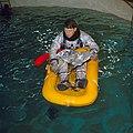 Wally Schirra floats on a one-man life raft during water egress training.jpg