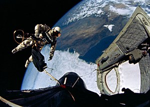 Gemini 4 - White floats away from the open hatch, towards the nose of the spacecraft at the beginning of the EVA
