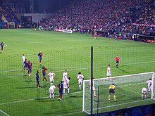 A photograph from behind the goal shows Barcelona and Wisła Kraków players gathering in the near penalty area for a corner kick. Wisła Kraków players are standing closer to the goal, and the referee is standing on the edge of the penalty area.