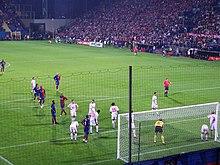 Une photographie de derrière le but montre les joueurs de Barcelone et de Wisła Kraków se rassemblant dans la surface de réparation proche pour un corner.  Les joueurs de Wisła Kraków se tiennent plus près du but et l'arbitre se tient au bord de la surface de réparation.