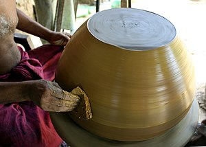 Yellowware - A yellowware clay pot is smoothed by a potter in Sri Lanka