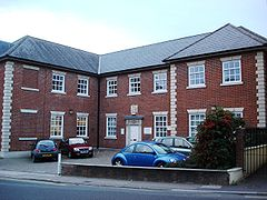 red brick building with small car park in front.