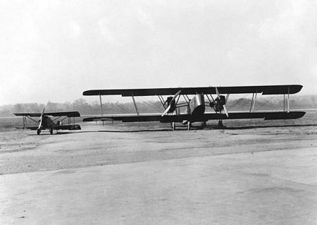 Two biplanes on a runway: a twin-engine in the foreground and a single-engine in the background